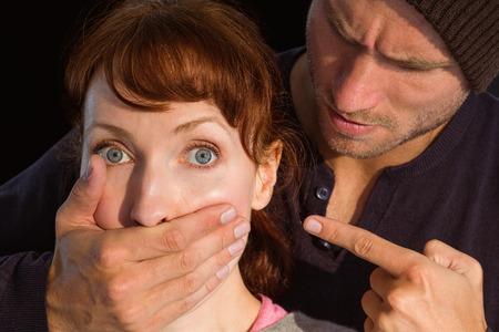 Man grabbing woman around mouth on black background photo