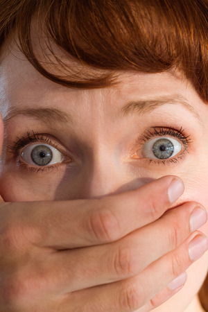 hijacker: Terrified woman with covered mouth on black background Stock Photo