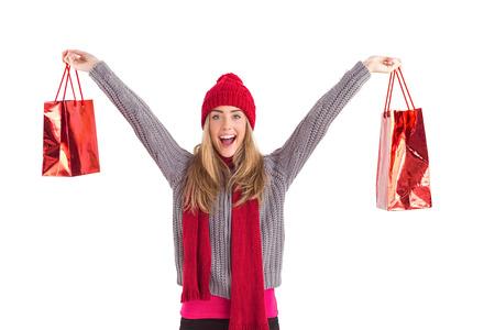 Festive blonde holding shopping bags on white background photo