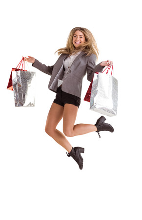 Stylish blonde jumping with shopping bags on white background photo