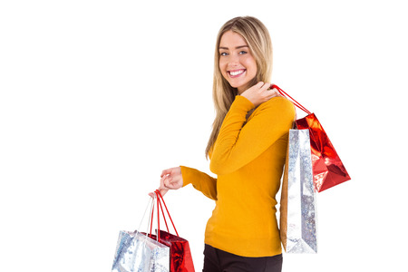 Stylish blonde smiling with shopping bags on white background photo