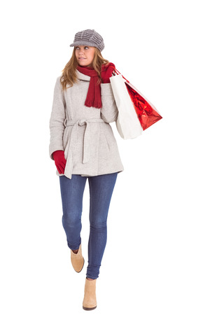 Happy blonde in winter clothes with bags on white background photo
