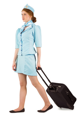 Pretty air hostess pulling suitcase on white background photo
