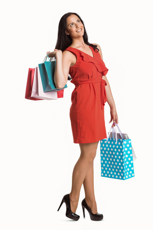 consumerism: Woman standing with shopping bags on white background Stock Photo