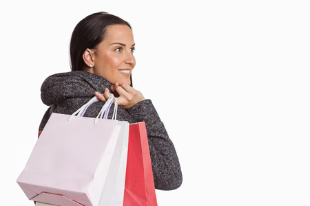 consumerism: Smiling woman holding shopping bag on white background