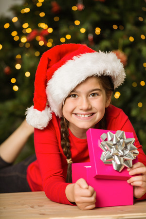 all under 18: Little girl opening a gift at christmas at home in the living room Stock Photo