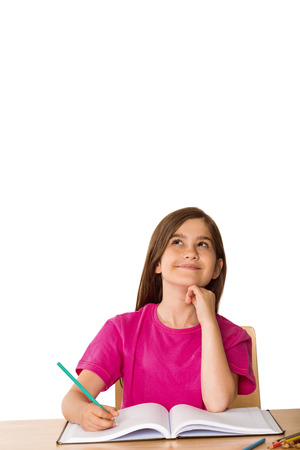 all under 18: Cute pupil working at her desk on white background