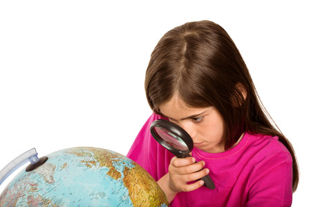 Cute pupil looking at globe through magnifying glass on white background photo