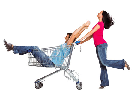 happy shopping: Young couple having fun with shopping cart on white background