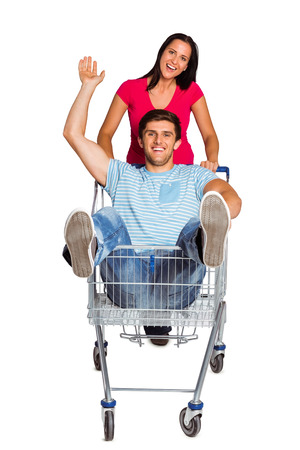 Young couple having fun with shopping cart on white background photo