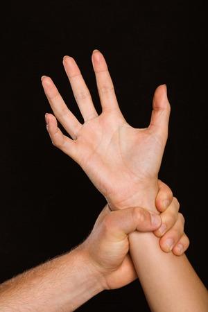 cowering: Male hand grabbing female wrist on black background