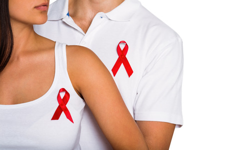 Couple supporting aids awareness together on white background photo