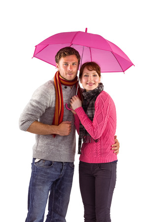 Couple standing underneath an umbrella on white background photo
