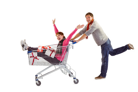 Man pushing woman in trolley on white background photo