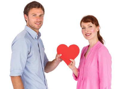 Couple holding a red heart on white background photo