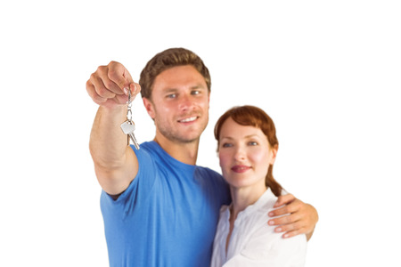 homeowners: Couple holding keys to home on white background