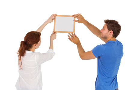 Couple deciding to hang picture on white background photo