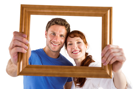 Couple holding frame ahead of them on white background photo