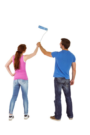 Couple painting a wall together on white background Stock Photo