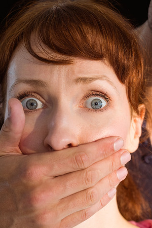 Terrified woman with covered mouth on black background Stock Photo