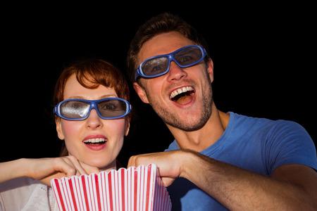 Couple enjoying a movie night in black background photo