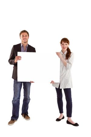 Smiling couple holding large sign on white background photo