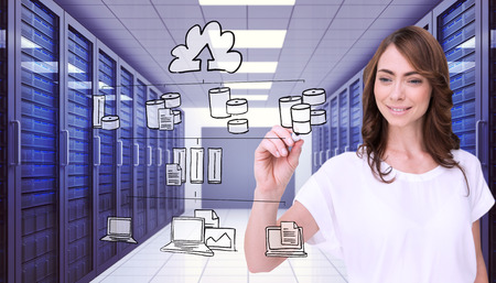 Smiling businesswoman holding marker against server room with towers photo