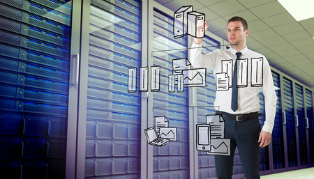 Young businessman writing with marker against server room photo