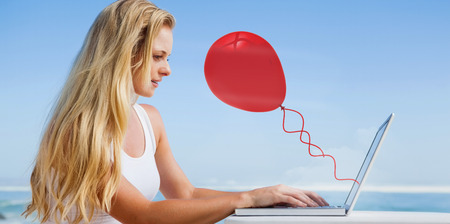 Composite image of pretty blonde using her laptop at the beach against red balloon photo