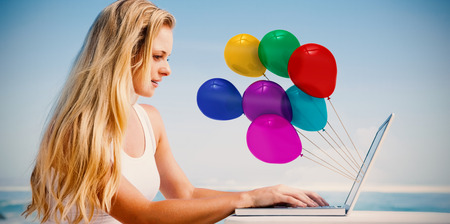 Pretty blonde using her laptop at the beach against colourful balloons photo