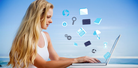 Composite image of pretty blonde using her laptop at the beach against app icons photo