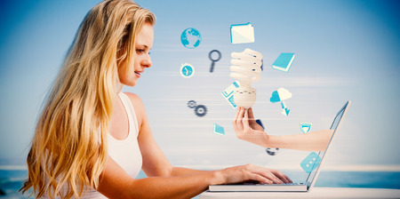 Composite image of pretty blonde using her laptop at the beach with hand holding bulb photo