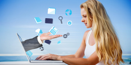 Composite image of pretty blonde using her laptop at the beach with hand presenting photo