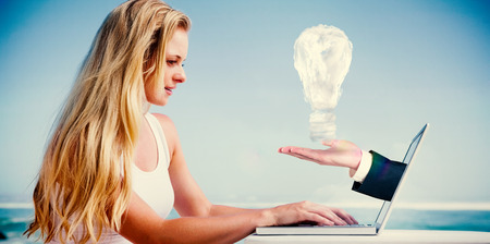Composite image of pretty blonde using her laptop at the beach with hand presenting cloud bulb photo