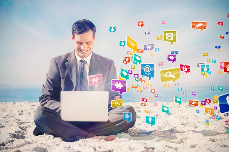 out of context: Young businessman with legs crossed typing on his laptop with colourful computer applications