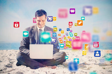 Young businessman with legs crossed typing on his laptop with colourful computer applications photo