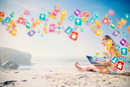 Gorgeous blonde in bikini using laptop on the beach with colourful computer applications photo