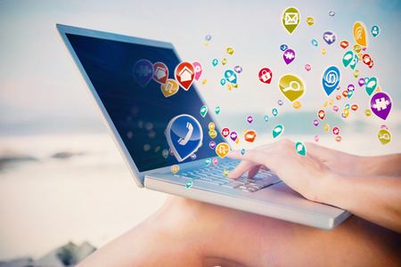 escapism: Woman sitting on beach using her laptop with colourful computer applications