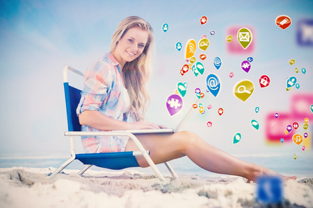 Pretty blonde sitting on beach using her laptop with colourful computer applications photo