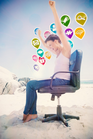swivel chair: Cheering brunette using laptop on the beach sitting on swivel chair with colourful computer applications