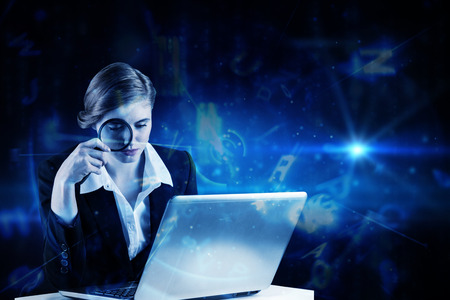 Redhead businesswoman using her laptop against blue background with letters photo