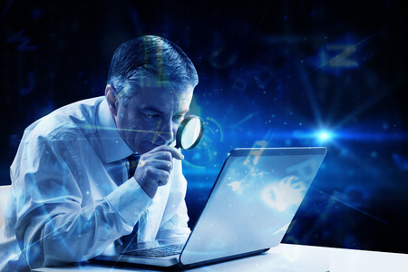 Mature businessman examining with magnifying glass against blue background with letters photo