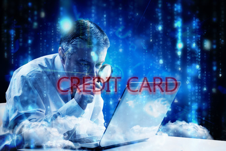 The word credit card and mature businessman examining with magnifying glass against lines of blue blurred letters falling photo