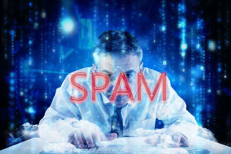 The word spam and mature businessman typing on keyboard against lines of blue blurred letters falling photo