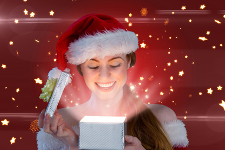 girl in santa costume opening a gift against bright star pattern on red photo
