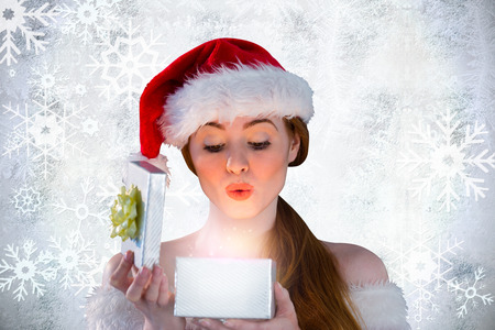 girl in santa costume opening a gift against silver snow flake pattern design photo