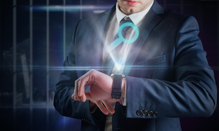 self discovery: Composite image of businessman using hologram watch against office overlooking city at night Stock Photo