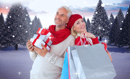 Happy festive couple with gifts and bags against snowy landscape with fir trees photo
