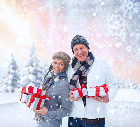 Festive mature couple holding christmas gifts against snowy landscape with fir trees photo
