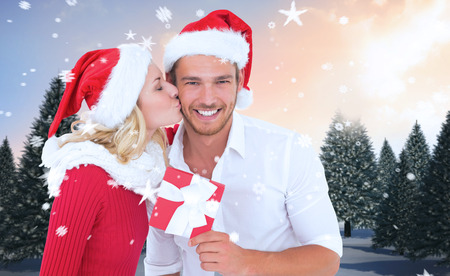 Young festive couple against snowy landscape with fir trees photo